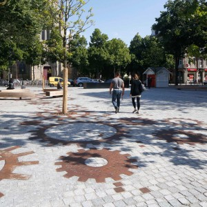 French studio Mutabilis paysage & urbanisme shared with us their project in Mulhouse, France. They transformed an ex parking lot into a vibrant square surrounded by busy streets of the old city. Metal cogs were placed as a part of granite pavement pattern since wheel has been the symbol of the Mulhouse city.