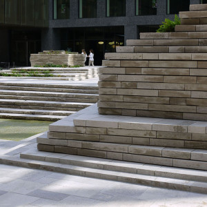 The courtyard, a compact cube of approximately 30 x 30 x 30 metres, embodies a sense of sanctity. It has been created through the convalescence of various architectural facades that stand in stark contrast to one another in terms of material and topographical design. These surfaces complement the light shell limestone floor, which is home to a built-in water feature. The ever-changing light reflects in dynamic patterns against the facades, imbuing the space with theatrical movement.