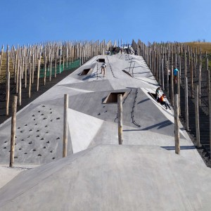 "Playscape be-Mine is about translation of industrial landscape to a playful recreational environment. Especially interesting is the concrete linear play element that much like the old mining shafts runs through an array of wooden slabs that were supporting the underworld. Furthermore, climbing on the concrete gets increasingly more difficult towards the top and requires some team work, which, according to the designers, acts ""as an immaterial reference to the hard physical work of the old mine-workers, who had to trust one another unconditionally"". Reaching the top immediately pays off the effort of climbing. A poetic and beautifully designed coal circle offers an epic view on the surrounding landscape, industrial remains and of course the coal. The storytelling is intelligently manifested through means of abstraction."